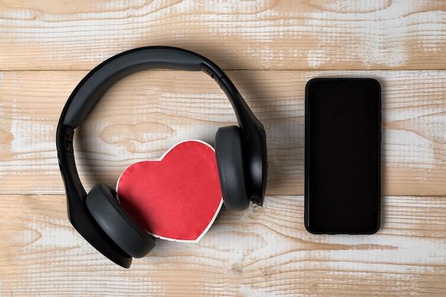 Беспроводные наушники в натуральную величину натянули маленькую красную коробочку в форме сердца и смартфон на светло-коричневом деревянном столе. прямо выше