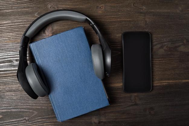 携帯電話と木製の背景の上にヘッドフォンが付いている本。オーディオブックのコンセプトです。トップビュー、コピースペース。