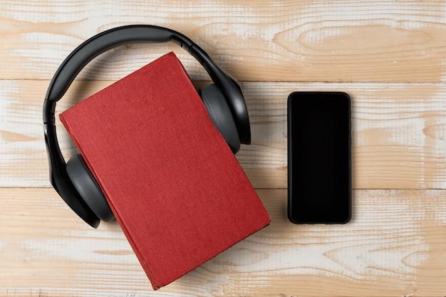 本、ヘッドフォン、木製の背景に電話。オーディオブックのコンセプトです。トップビュー、コピースペース