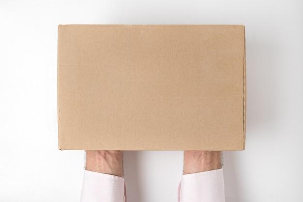 Прямоугольная коробка на руках мужчин на белом фоне. прямо над макетом