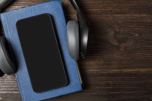 ヘッドフォンで本の上に横たわる携帯電話。オーディオブックのコンセプトです。暗い木製の背景コピースペース。