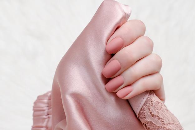 Бледно-розовая атласная ткань в женской руке. салон маникюра.