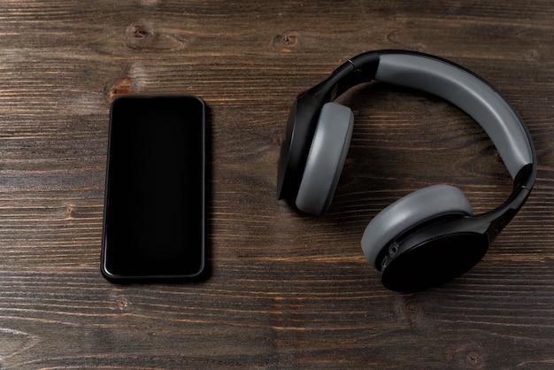 Наушники и телефон на темном деревянном фоне. гаджеты современного человека.