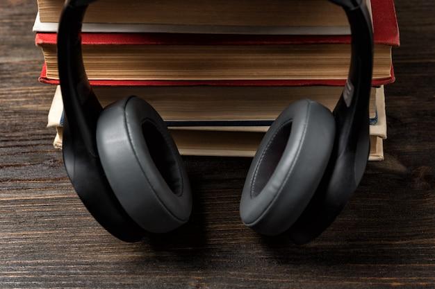本とヘッドフォン。オーディオブックのコンセプトを使用して学習。すばやく暗記。