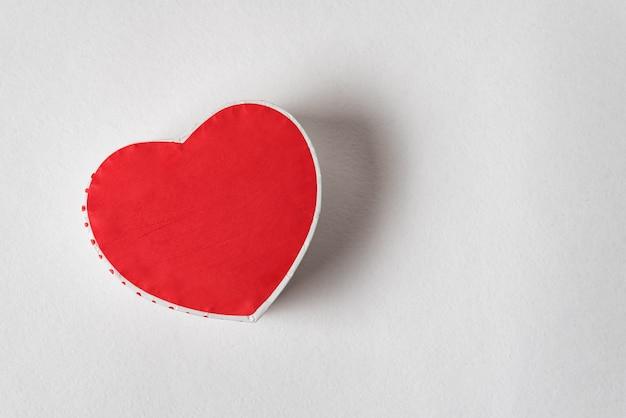 Коробка красного сердца форменная на белой предпосылке. копировать пространство прямо выше. подарок на день святого валентина