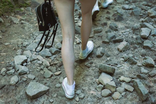 女性の足は岩だらけの道を行きます。山へのハイキング。閉じる