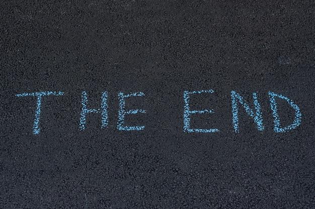 Слово конец написано мелом на асфальте. надпись на асфальте.