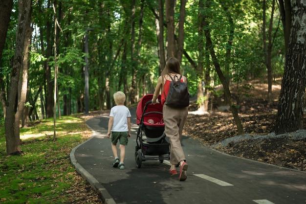 息子とベビーカーで赤ちゃんと一緒に公園を歩いて若い母親。子供と一緒に歩きます。母性のコンセプトです。背面図