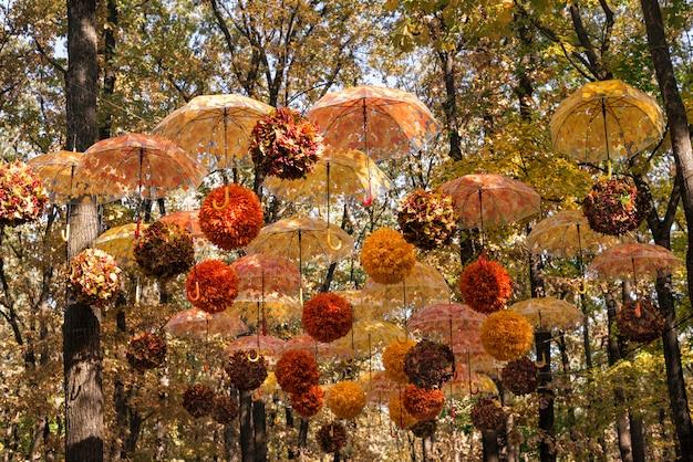 Оформление парка живыми цветами. осенний парк украшен зонтиками и цветочными композициями