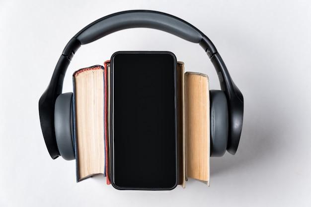 ステレオヘッドフォン、書籍、白い背景の上の電話。オーディオブックのコンセプトです。コピースペース