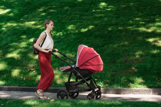 公園で乳母車を歩いて若い母親。赤ちゃんと一緒に新鮮な空気の中を歩きます。