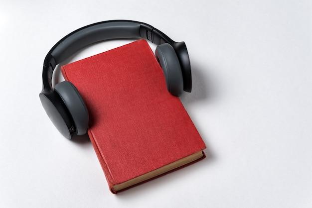 白い背景の上のイヤホンと赤い本。オーディオブックのコンセプトで学びます。コピースペース