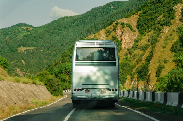 Задняя сторона автобуса. вид сзади. пустой белый автобус на горном шоссе.
