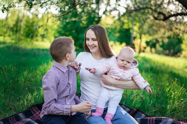 Мать играет с детьми в парке. старший сын и маленькая дочь. весенний день