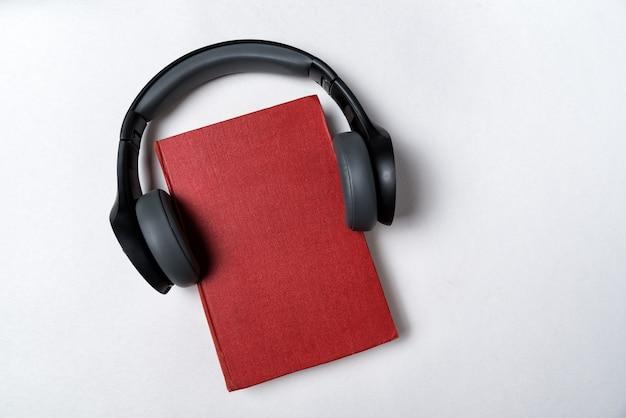 白い背景の上のヘッドフォンで赤い本。オーディオのコンセプトで学びます。コピースペース