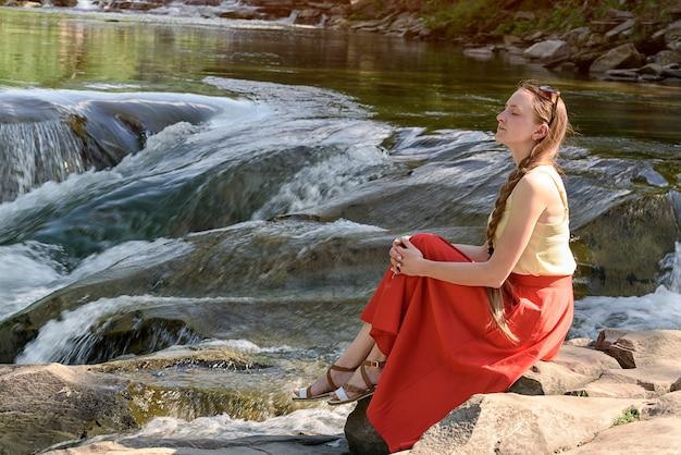 山の川のカスケードの岩の上に座っている赤いスカートの美しい長い髪の少女