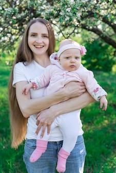 自然を手に小さな娘を持つ若い母親。縦枠