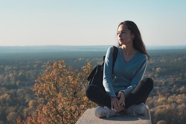 Красивая молодая женщина, сидя на вершине холма и смотрит вдаль. путешествие на выходные.