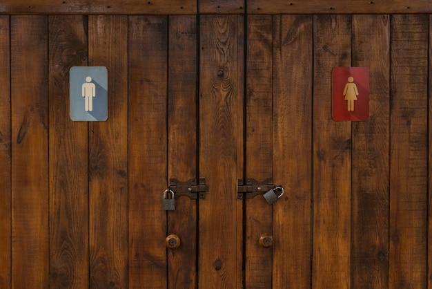 バスルームへの木製のドア。女性と男性のトイレ。荒い木の質感