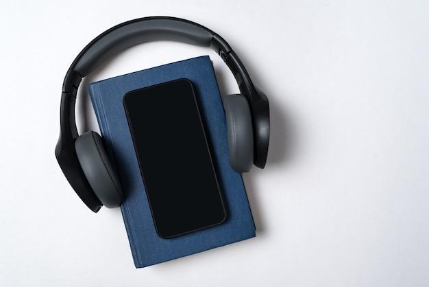 ブルーブック、ヘッドフォン、電話。電子書籍とオーディオブックのコンセプト。白い背景のコピースペース。