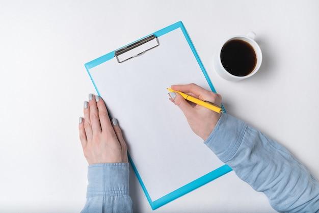 Взгляд сверху женских рук, листа бумаги и чашки кофе. женщина пишет на бумаге. копировать пространство, фоновый рисунок