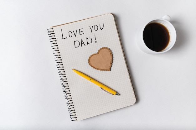 Обратите внимание, я люблю папу в блокноте. слова написаны от руки. день отца