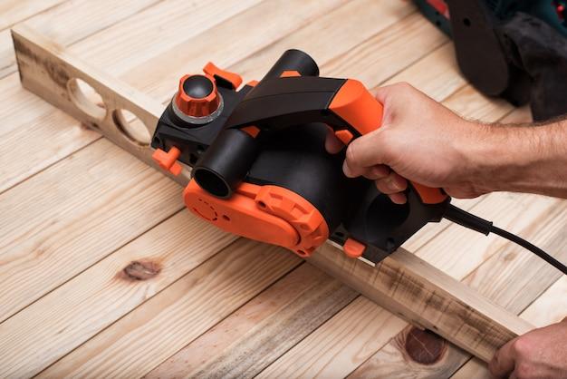 Электрический рубанок в мужской руке. обработка заготовки на светло-коричневом деревянном столе.