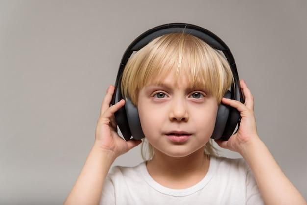 Белокурый подросток мальчика с наушниками на светлой стене. подросток слушает музыку. портрет