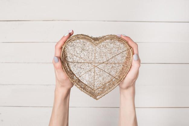 Женские руки держат металлическую проволоку прозрачную коробку в форме сердца