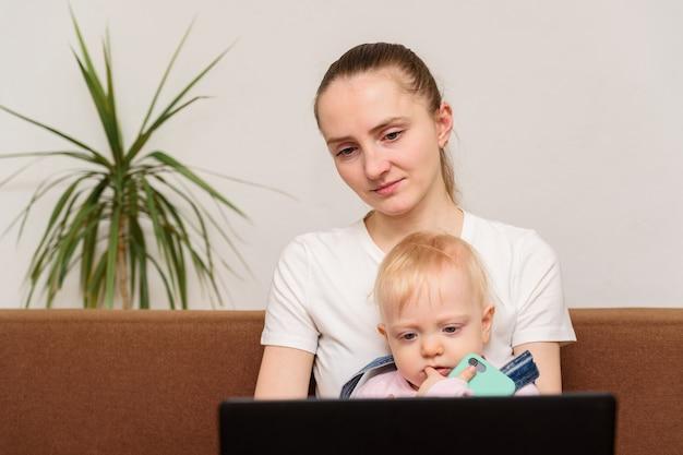 赤ちゃんを持つ若い母親がモニターを見てください。子供にコンピュータを害する
