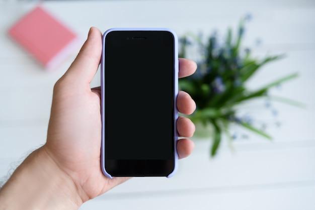 スマートフォンで男性の手。