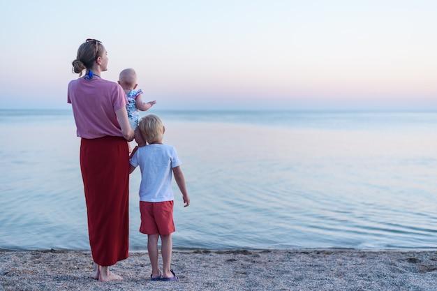 Молодая мать с ребенком и старший сын стоять на берегу моря. вид сзади семья на пляже на закате