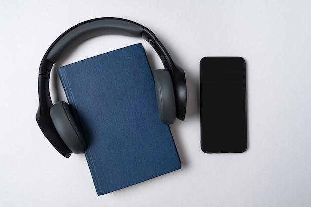 スマートフォン、テーブルの上のハードカバーの本とヘッドフォン。本のコンセプトを聞いてください。コピースペースの上面図