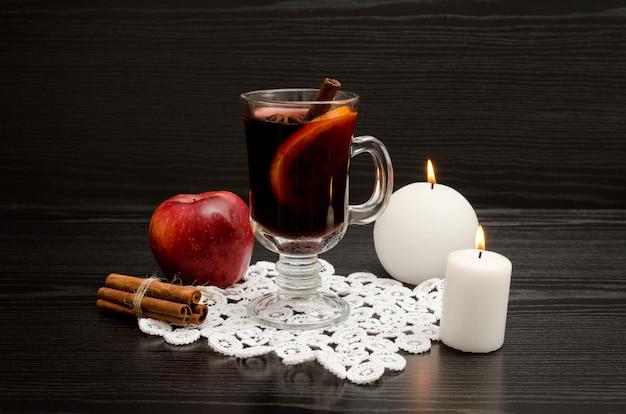 Глинтвейн со специями на кружевной салфетке. белые свечи, палочки корицы и яблоко. черный деревянный фон