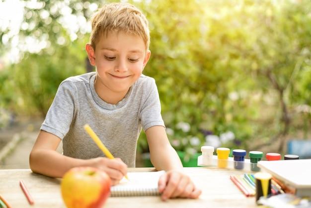 かわいい男の子は鉛筆静物で描画します。オープンエア。バックグラウンドでの庭。創造的なコンセプトです。