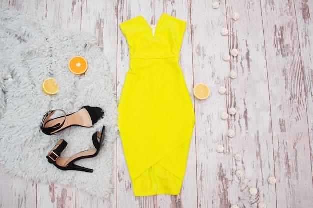 Ярко-желтое платье, черные туфли и цитрусовые на меху. фонари, светлый деревянный фон. модная концепция, вид сверху