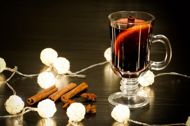 Кружка глинтвейна со специями, палочки корицы, звездчатого аниса. подсветка ротанговых фонарей на черном деревянном столе