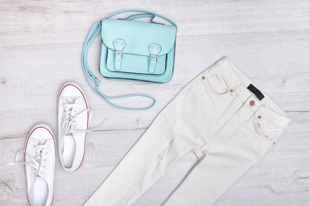 白のジーンズとスニーカー、ミントバッグ。ファッショナブルなコンセプト。木製の背景。