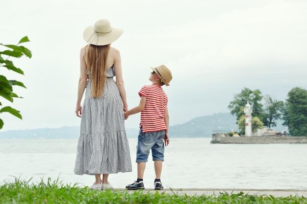 ママと息子が桟橋に立っています。背景、灯台、遠くの山々の海。背面図
