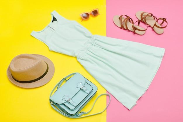 女性のワードローブ。ミントドレス、ハンドバッグ、靴、帽子。明るいピンクがかった黄色の背景。ファッションコンセプト