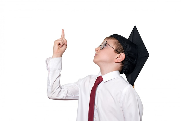 正方形の学術帽子と眼鏡の少年は彼の指を上向きにします。