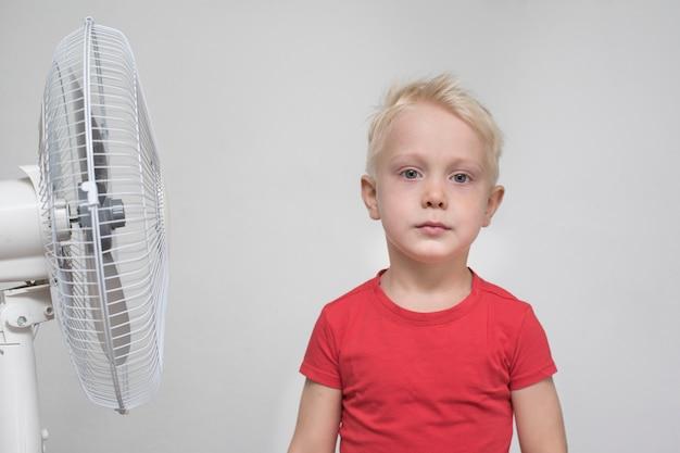 Довольно белокурый мальчик в красной рубашке стоит возле вентилятора.