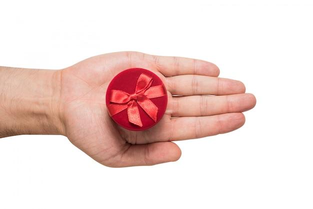 丸い赤いジュエリーボックスで男性の手のひらを開きます。プレゼント。