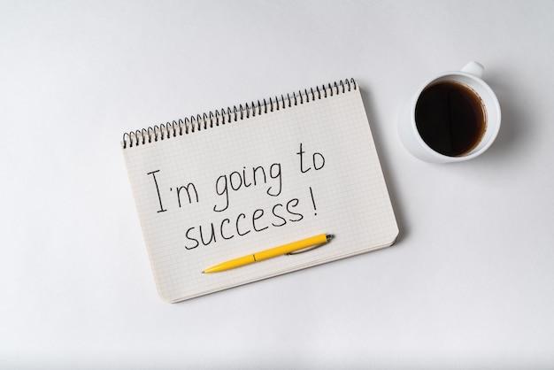 Я иду к успеху надпись. блокнот, ручка и чашка кофе.