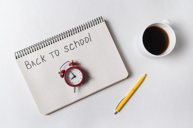 Надпись в тетради обратно в школу. старинный будильник и чашка кофе