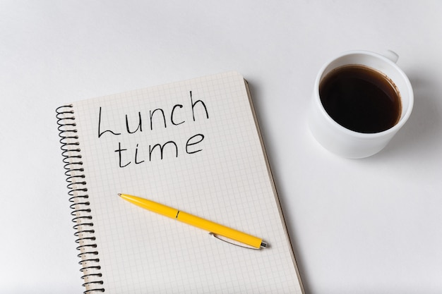 Тетрадь с надписью время обеда. чашка кофе и ручка на белом фоне