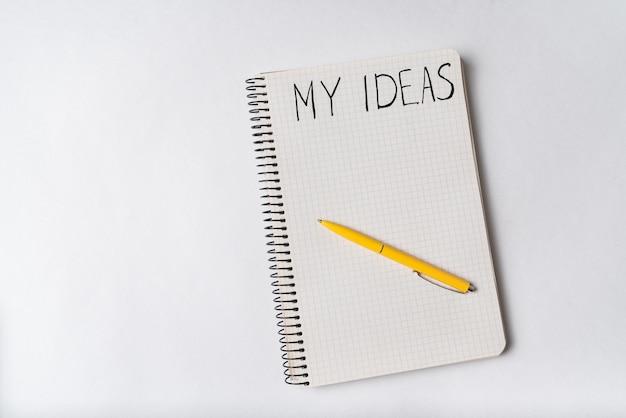 Блокнот со словами мои идеи на белом фоне. вид сверху, ручка на блокноте