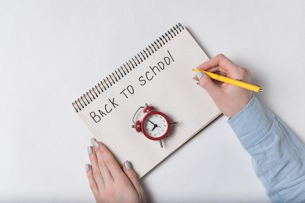 Надпись в тетради обратно в школу. женские руки, писать в блокноте. вид сверху ноутбука, руки и винтажный будильник