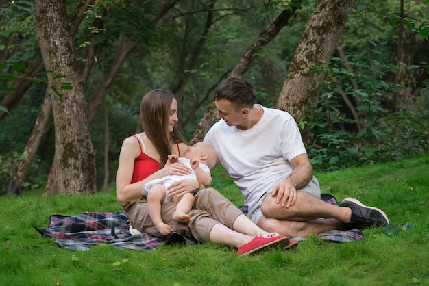 幸せな家族は屋外のピクニックを持っています。若いお母さんお父さんとピクニック毛布の上に座って生まれたばかりの赤ちゃん。