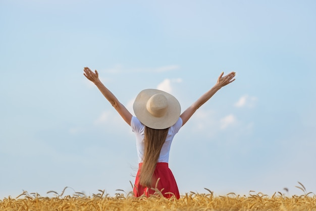 Молодая дама в шляпе, прогуливаясь по пшеничному полю и поднял руки вверх. гендерное равенство и независимость